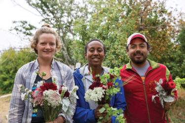 Marianne Olney-Hamel, Moretta Browne, and Edgar Flores, apprentices with the Apprenticeship in Ecological Horticulture program, arrange flowers for the Farm & Garden Market Cart at the base of campus.
