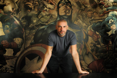 Axel Alonso stands in front of a mural of Captain America