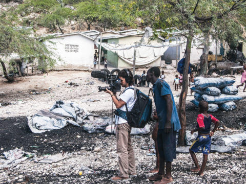 Filmmaker Juan Mejia films a dilapidated market in Haiti as on-lookers watch him curiously.