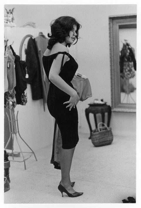 Woman trying on a black dress.